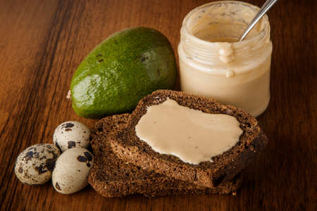 top view closeup glass jar wiht tahini butter, rye bread slices, whole avocado, and quail eggs on wooden background