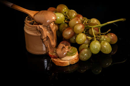 closeup chocolate peanut butter in glass jar with wooden spoon on top served with small cracker and green grapes Banco de Imagens