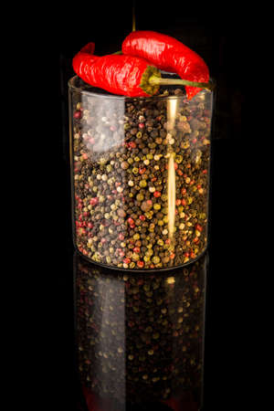 tall glass jar with assorted peppercorns and two whole red chili peppers over black background 写真素材