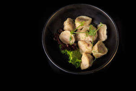 top view of boiled meat dumplings of wholemeal flour with fresh salad leaves in deep gray bowl on black background
