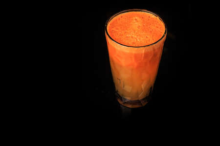 tasty fresh raw vegetable carrot juice in tall faceted plastic glass stands on black background