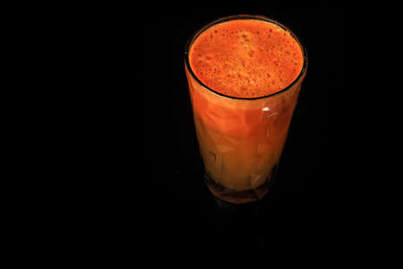 delicious fresh raw carrot juice in tall faceted plastic glass stands on black background
