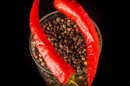 macro view of tall glass jar with assorted peppercorns and two whole red chili peppers over black background