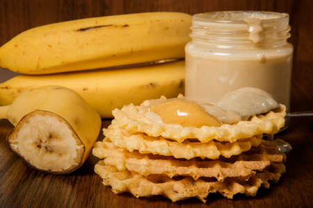 closeup tahini butter jar, whole and half of bananas, belgian waffles with tahini and honey on wooden background Stok Fotoğraf