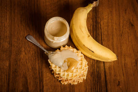 Top view on tahini butter jar, one banana, spoon on Belgian waffles with tahini and honey on wooden background