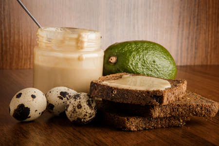 Closeup glass jar with tahini butter, spoon, rye bread, whole avocado, and three quail eggs on wooden background