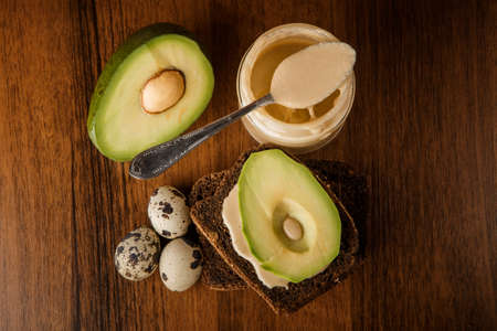 top view on tahini butter in glass jar with spoon, quail eggs, rye bread slices and sliced avocado on wooden background