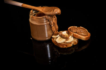 Top view on creamy peanut butter in a glass jar, in wooden spoon, and on two small crackers on black background
