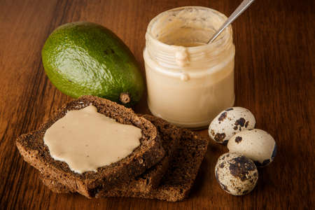 Top view closeup glass jar with tahini butter, sliced rye bread, whole avocado, and three quail eggs on wooden background