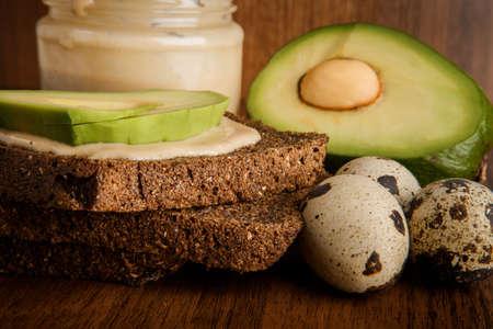 Macro of sliced avocado on rye bread slices, three quail eggs and tahini glass jar on wooden background