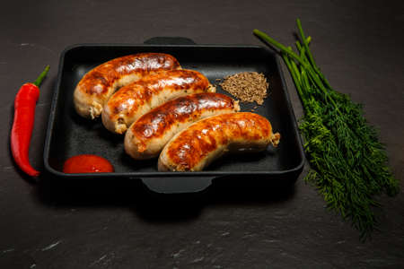 square pan with four fried sausages, ketchup, caraway seeds, green dill, and red chili pepper served on black background