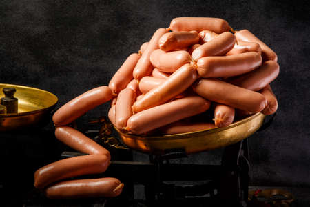 large heap of raw long thin wieners with natural casings served on antiquarian scales over black background Stock Photo