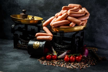pile of uncooked long thin wieners on antiquarian scales served with sliced onion and tomatoes cherry Stock Photo