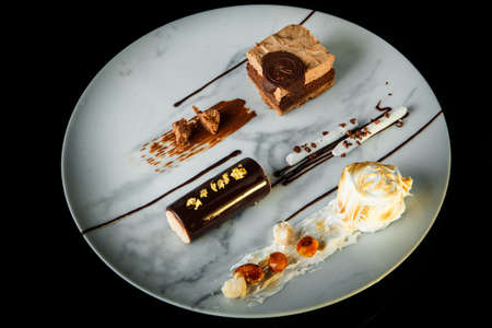 top view of delightful chocolate and white cream mousse dessert served on round plate on black background Stock fotó