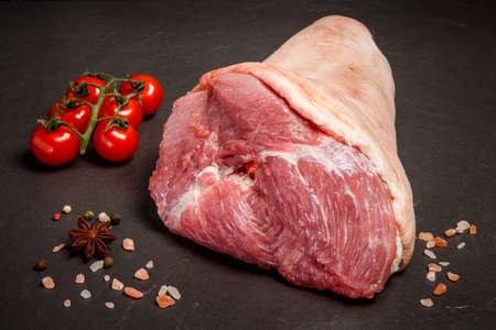 Nahaufnahme großes rohes Bein mit Fleisch serviert mit rosa Salz, verschiedenen Gewürzen und Tomaten-Kirsche auf schwarzem Hintergrund Standard-Bild