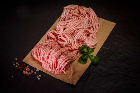 top view of raw minced meat served on craft paper with assorted spices and green basil leaf on black background