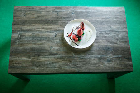 top view on white round restaurant plate with delicious dessert stands on dark wooden table on green background