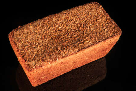 top view closeup rectangular rye bread with sesame seeds decoration on top served on black background