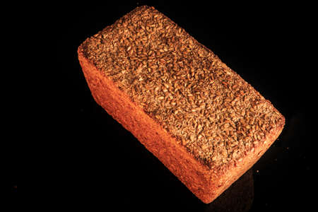 whole loaf of rectangular rye bread with sesame seeds decoration on top served on black background