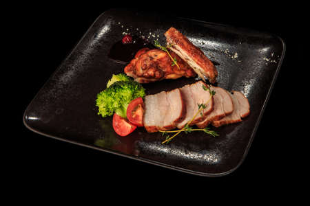 smoked meat slices and chicken pieces served with rosemary, broccoli, tomatoes, and sauce on black restaurant plate