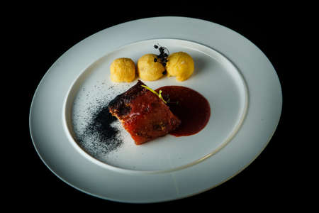 top view of roasted meat and potato balls decorated with spicy red sauce and dry herbs on white plate over black