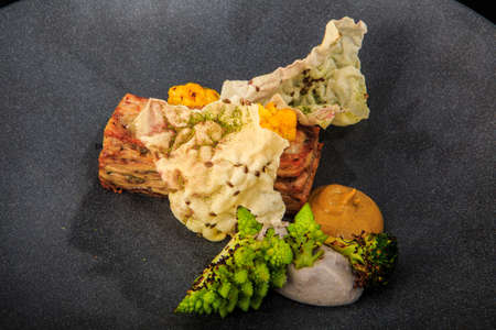 closeup modern meat dish with assorted sauces and vegetables served on gray plate on black background Zdjęcie Seryjne