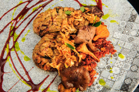 top view closeup animal brain with mushrooms and meat served with herbs and sauces on original restaurant plate 写真素材 - 129269685