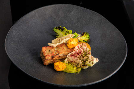 tasty restaurant meat dish with assorted sauces and vegetables served on gray plate on black background Zdjęcie Seryjne