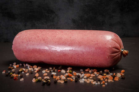 beef sausage served in big thick stick with pink salt and assorted spices on black background