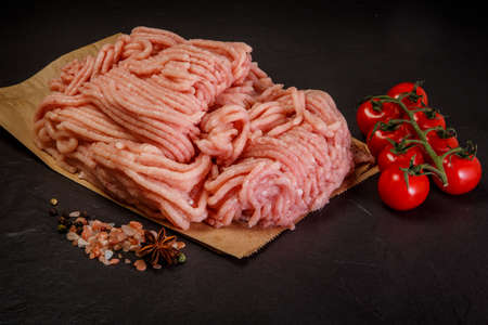 fresh raw forcemeat served on craft paper with assorted spices and tomatoes cherry on black background Zdjęcie Seryjne