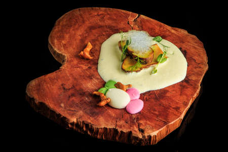 top view on exquisite decorated restaurant dish of assorted mushrooms, sauces, and greens served on original wooden board on black background