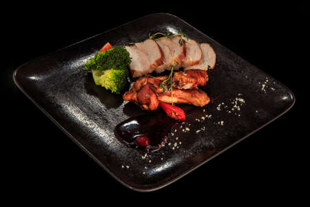 top view of tasty smoked meat and chicken pieces with broccoli, tomatoes, and sauce on black restaurant plate Zdjęcie Seryjne
