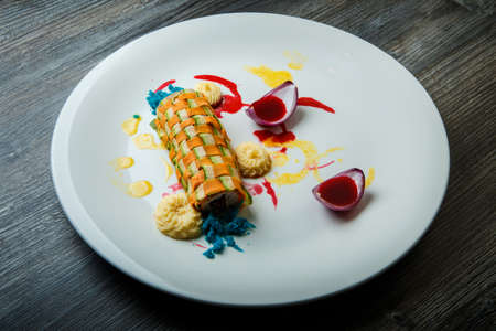 originally decorated vegetable roll stuffed with minced meat served with assorted sauces on white plate on wooden table