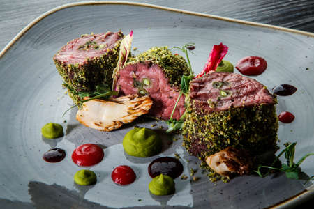 closeup exclusive decorated three raw baked meat pieces served with assorted sauces on modern white restaurant plate on wooden table Zdjęcie Seryjne