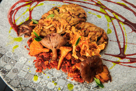 top view closeup goat brain with mushrooms and meat served with herbs and sauces on original restaurant plate 写真素材