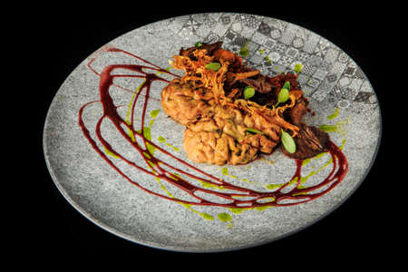 top view of lamb brain with mushrooms and meat served with herbs and sauces on original plate on black background