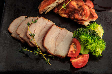 top view closeup smoked meat and chicken pieces with broccoli, tomatoes, and sauce on black restaurant plate