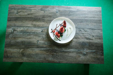 top view on white round restaurant plate with elegant dessert stands on dark wooden table on green background