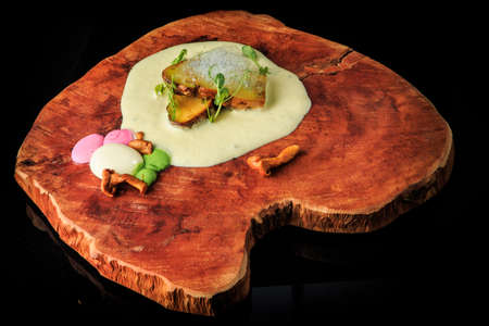 trendy restaurant appetizer of assorted mushrooms, sauces, and greens served on original wooden board on black background Stok Fotoğraf