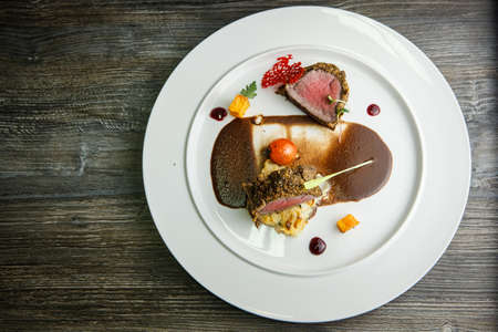 top view on finely decorated medium raw grilled meat pieces with brown sauce on modern white round plate on wooden table