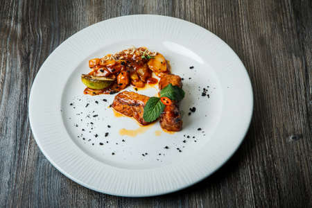 finely decorated with sauce and greens barbecue meat pieces served with baked potato on white restaurant dish on wooden table Zdjęcie Seryjne