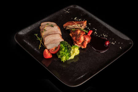 smoked bacon slices and chicken pieces with rosemary, broccoli, tomatoes, and sauce on black restaurant plate Zdjęcie Seryjne