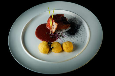 big piece of tasty meat and potato balls decorated with spicy red sauce and dry herbs on white plate over black