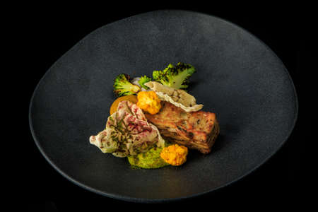 top view of delicious meat dish with assorted sauces and vegetables served on gray plate on black background