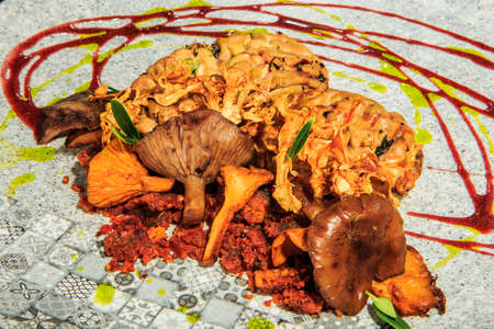 closeup baked animal brain with mushrooms and meat served with herbs and sauces on original restaurant plate