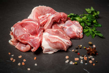 top view on heap of small meat pieces served with pink salt, assorted spices and green parsley on black background