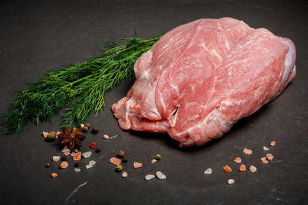 large piece of raw meat served with pink salt, assorted spices and fresh green dill on black background Zdjęcie Seryjne