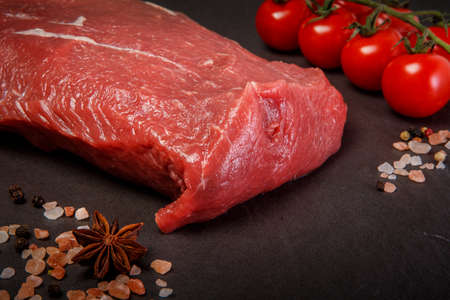 closeup large tenderloin marbled raw meat served with assorted spices and tomatoes cherry on black background