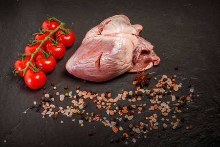 top view on large raw heart served with pink salt, assorted spices and tomatoes cherry on black background