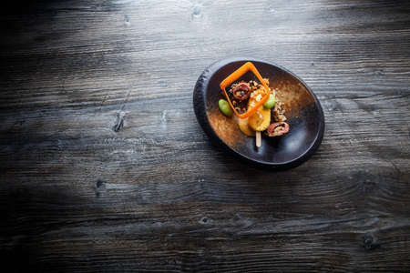top view on exclusive fish dish with beautiful garnish decoration served in original black plate on wooden table